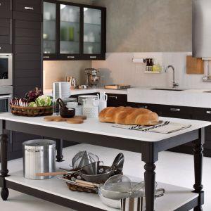 Ciemne meble kuchenne dobrze komponują się z białym blatem. W eleganckiej kuchni przyda się dodatkowy blat roboczy, a może być nim elegancki stół ustawiony w centralnym punkcie pomieszczenia. Fot. Elmar Cucine