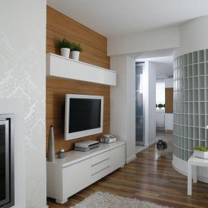 Białe szafki oraz biały odbiornik telewizyjny wyglądają bardzo elegancko na tle ściany wykończonej drewnem. Projekt: Małgorzata Mazur. Fot. Bartosz Jarosz