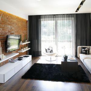 Ścianę w salonie wykończono cegłą. Biała szafka RTV dodaje wnętrzu lekkości. Projekt: Małgorzata Mazur. Fot. Bartosz Jarosz