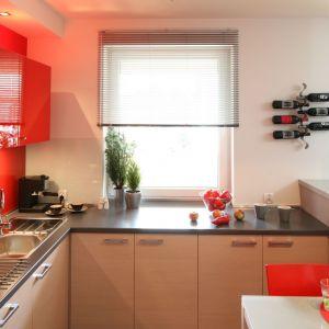 Czerwone górne szafki ożywiły stonowaną kolorystykę kuchni. Projekt Marta Kruk. Fot. Bartosz Jarosz