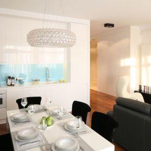 Aneks kuchenny i salon, które są ze sobą połączone warto urządzić w jednym stylu. Można dodać element kontrastujący, np ciekawie wykończyć ścianę nad blatem. Projekt: Anna Maria Sokołowska. Fot. Bartosz Jarosz