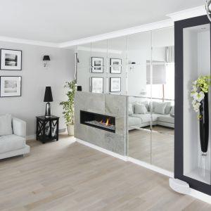 Lustra to najprostszy sposób na powiększenie przestrzeni. Szklana ściana w salonie sprawi, że wnętrze będzie nie tylko stylowe, ale również bardziej świetliste. Projekt: Magdalena Smyk. Fot. Bartosz Jarosz