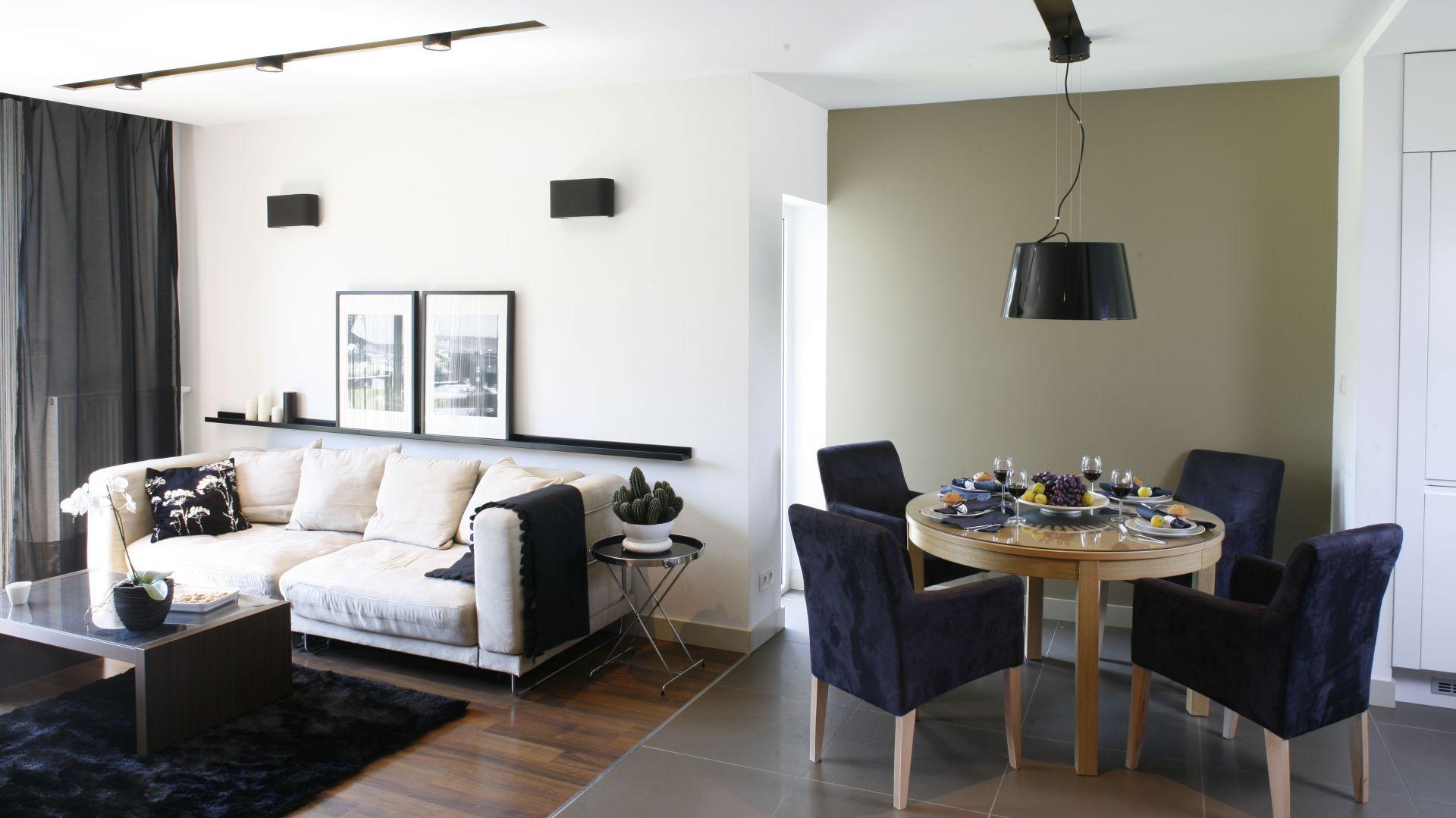 Miękkie, tapicerowane krzesła zestawione z okrągłym, drewnianym stołem dają ciekawy efekt wizualny. Projekt: Małgorzata Mazur. Fot. Bartosz Jarosz