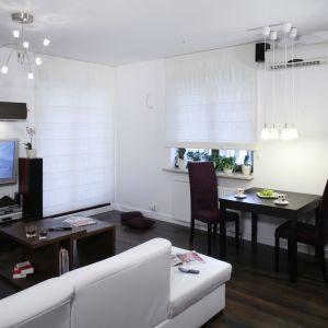 Mały, kwadratowy stół ustawiony bezpośrednio przy ścianie to świetne rozwiązanie jeśli nasz salon jest mały. Projekt: Ewa Para. Fot. Bartosz Jarosz