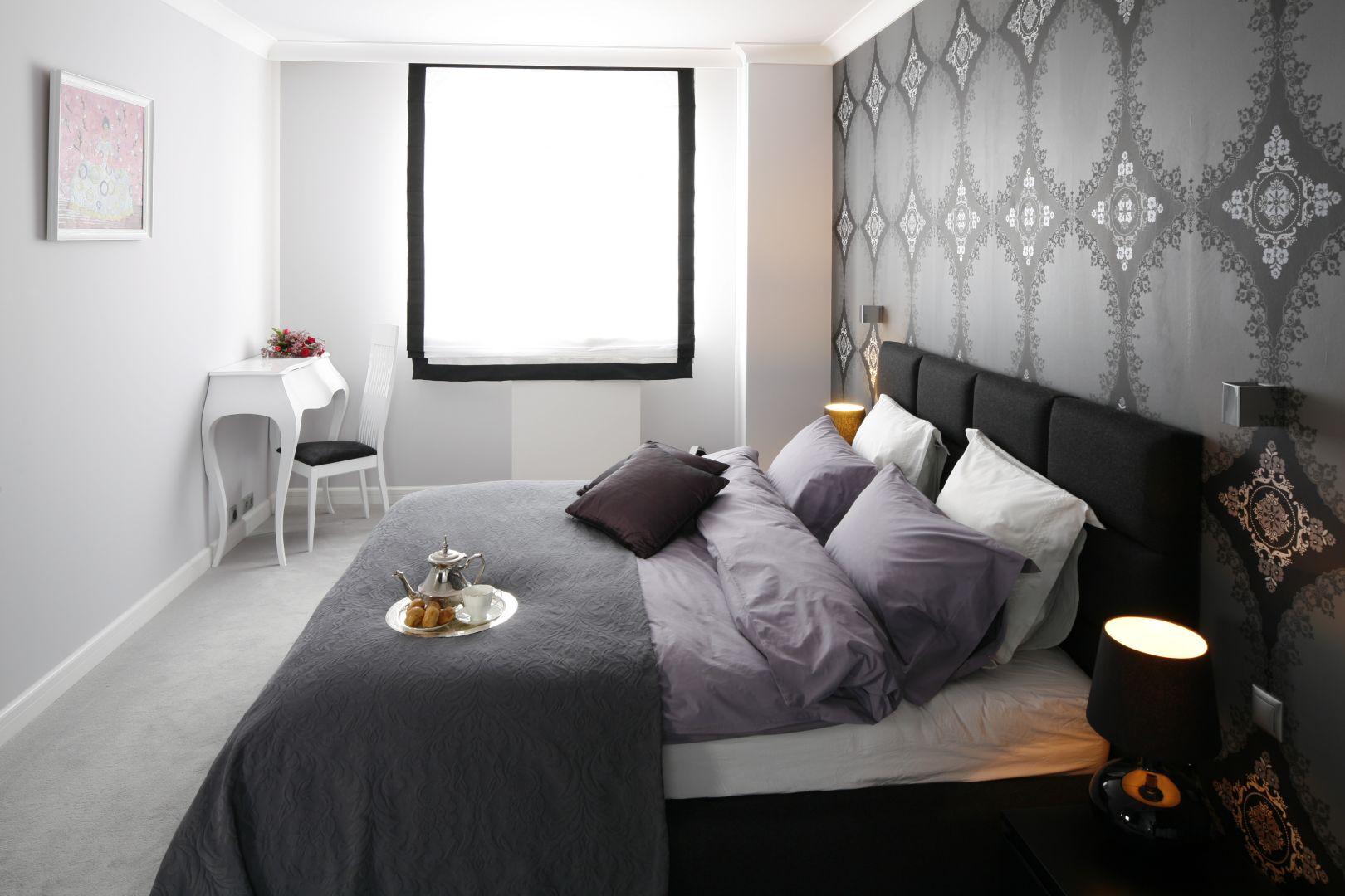 Miękkie, duże łóżko to niezbędny element wyposażenia każdej sypialni. Wygodnym rozwiązaniem jest wybór modelu z tapicerowanym zagłówkiem. Taki rodzaj łóżka doskonale prezentuje się na tle wzorzystej tapety. Projekt: Magdalena Smyk. Fot. Bartosz Jarosz