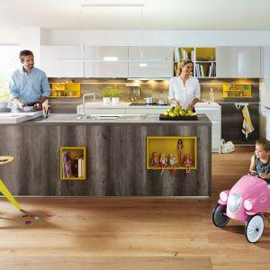 Drewno doskonale łączy się z wszelkimi kolorami. W tej kuchni lekko szary fornir połączono z żółtym słonecznym kolorem, stosując go jako półki/kubiki w wyspie oraz otwarte półki w zabudowie. Dzięki temu kuchnia zyskała więcej energii. Fot. Schueller