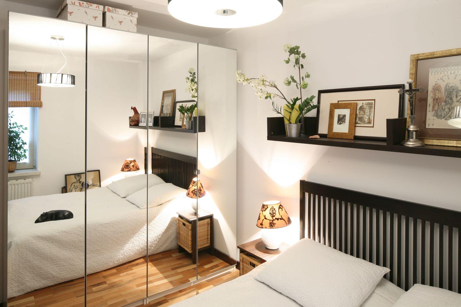 Najprostszym sposobem na powiększenie małej sypialni, jest umocowanie lustra na drzwiach szafy. Optycznie powiększa ono wnętrze i dodaje mu więcej światła. Projekt: Marcin Lewandowicz. Fot. Bartosz Jarosz