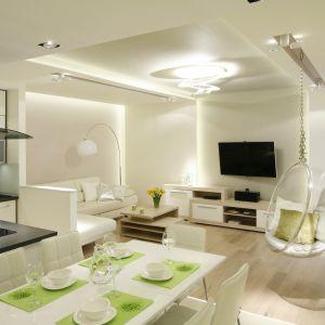 Salon i kuchnia urządzone na biało sprawią, że wnętrze będzie jasne, rozświetlone i niezwykle przestrzenne. Projekt: Marta Kilan. Fot. Bartosz Jarosz