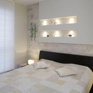 Jasna sypialnia w minimalistycznym stylu. Nad łóżkiem umieszczono niewielkie wnęki, które ładnie podświetlono. To świetne miejsce na subtelne dekoracje, pamiątki oraz zdjęcia. Projekt: Katarzyna Mikulska-Sękalska. Fot. Monika Filipiuk-Obałek