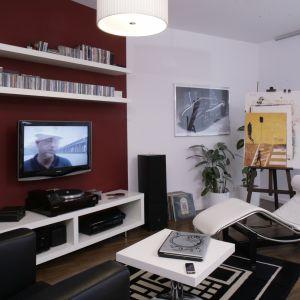Białe półki umieszczone nad odbiornikiem telewizyjnym, to idealne miejsce na przechowywanie ulubionych filmów i płyt DVD. Projekt: Michał Mikołajczak. Fot. Bartosz Jarosz