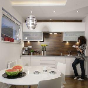 Kuchnia z jadalnią została urządzona wygodnie i funkcjonalnie. Trzy, a nawet cztery osoby mogą swobodnie zjeść posiłek. Biały stół wygląda świeżo i optycznie powiększa przestrzeń oraz efektownie kontrastuje z drewnianą ścianą nad blatem. Projekt: Michał Mikołajczak. Fot. Bartosz Jarosz