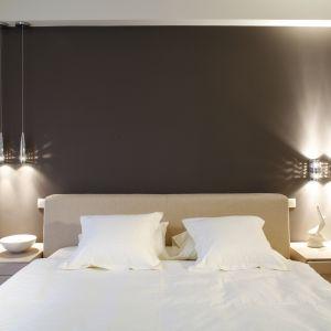 Sypialnia utrzymana w beżowej tonacji, urozmaicona fioletem. Miękkie, tapicerowane łóżko zapewnia komfort wypoczynku. Lampki nad łóżkiem tworzą we wnętrzu klimatyczny nastrój. Projekt: Joanna Wysocka. Fot. Bartosz Jarosz