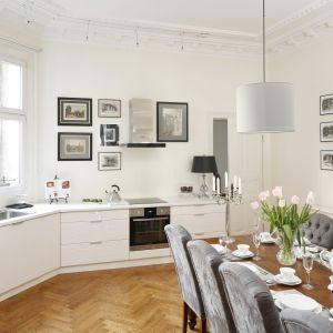Elegancka kuchnia z jadalnią. Zamiast górnych szafek na ścianie zawisła galeria stylowych obrazów. Projekt: Iwona Kurkowska. Fot. Bartosz Jarosz