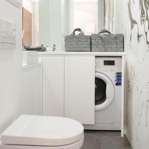 Schowanie pralki w zabudowie sprawi, że wnętrze łazienki będzie wydawało się prostsze i niezabałaganione. Biel na ścianach i na meblach sprawi zaś, że wnętrze będzie wyglądać na większe. Projekt: Karolina Łuczyńska. Fot. Bartosz Jarosz