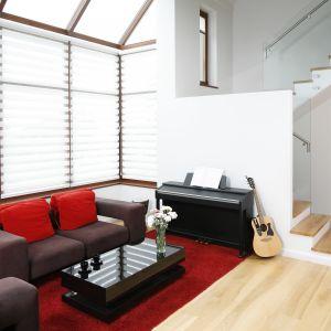 Jasny salon w domu jednorodzinnym. Mocnym akcentem wnętrza jest kolorowa sofa, która wyróżnia się geometryczną formą. Projekt: Michał Mikołajczak. Fot. Bartosz Jarosz