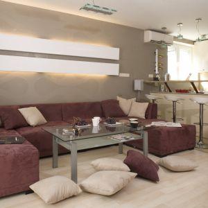 Urządzając salon większość z nas decyduje się na meble w stonowanym, uniwersalnym kolorze. Popularnością cieszą się zwykle beże, brązy i szarości, a przecież fioletowa sofa to świetny sposób na ocieplenie i urozmaicenie wnętrza. Projekt: Maciej Twaróg. Fot. Monika Filipiuk-Obałek