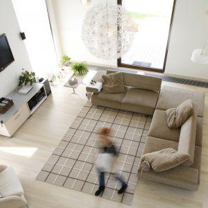 Jest wiele sposobów na wizualne ocieplenie wnętrza rodzinnego salonu. Można posłużyć się kolorem, światłem lub tkaninami. Projekt: Alina Grzybowska, Konstanty Jeżewski. Fot. Monika Filipiuk-Obałek
