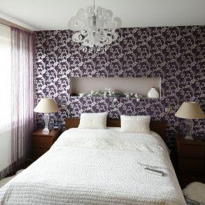 Także w małej sypialni możemy zaskakiwać. Ciekawym elementem wnętrza będzie np. ściana za łóżkiem wykończona dekoracyjną tapetą. Drewniane łóżko oraz stoliki nocne świetnie dopełniają kompozycję.  Projekt: Piotr Stanisz. Fot. Bartosz Jarosz