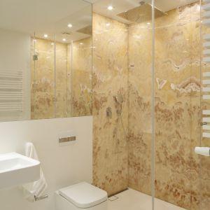 Naturalne materiały prezentują się doskonale również na mniejszych powierzchniach. W tej łazience na ścianie za prysznicem umieszczono prawdziwy onyks, który swoją złotą barwą odwraca uwagę od małego metrażu wnętrza. Projekt Katarzyna Kiełek, Agnieszka Komorowska-Różycka. Fot. Bartosz Jarosz