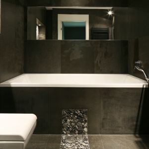Nawet niewielka łazienka urządzona w czerni i mocnych szarościach może prezentować się stylowo. Wystarczy zastosować naturalne materiały i lustra, które optycznie powiększą wnętrze. Projekt: Jarosław Jończyk, Monika Włodarczyk. Fot. Bartosz Jarosz
