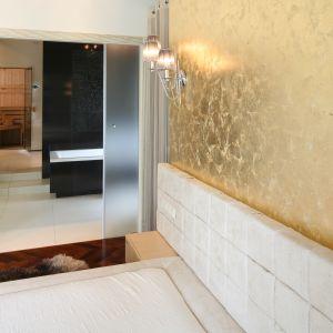 Drzwi z mlecznego szkła pozwalają zachować prywatność w łazience, jednak są na tyle delikatne, że nie tworzą bariery między łazienką a sypialnią. Projekt: Dominik Respondek. Fot. Bartosz Jarosz