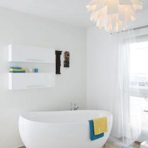 Śliczna biała łazienka z wolnostojącą wanną. Ciekawym elementem aranżacji jest dekoracyjna lampa oraz dodatki w turkusowym kolorze. Projekt: Katarzyna Uszok. Fot. Bartosz Jarosz