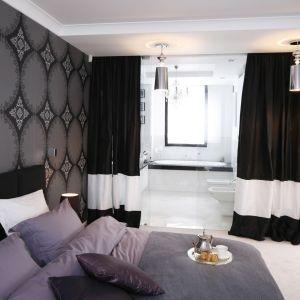 Łazienka urządzona w bieli, jednak równie stylowa jak sypialnia, została zasłonięta grubymi zasłonami. Dzięki temu zapewni prywatność, ale w każdej chwili można ją całkowicie otworzyć na sypialnię. Projekt: Magdalena Smyk. Fot. Bartosz Jarosz