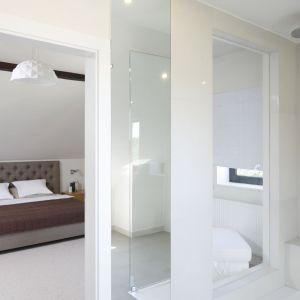 W tym wnętrzu ciekawym elementem spajającym sypialnię z łazienką jest szyba umieszczona w ścianie prysznica. Projekt: Kamila Paszkiewicz. Fot. Bartosz Jarosz