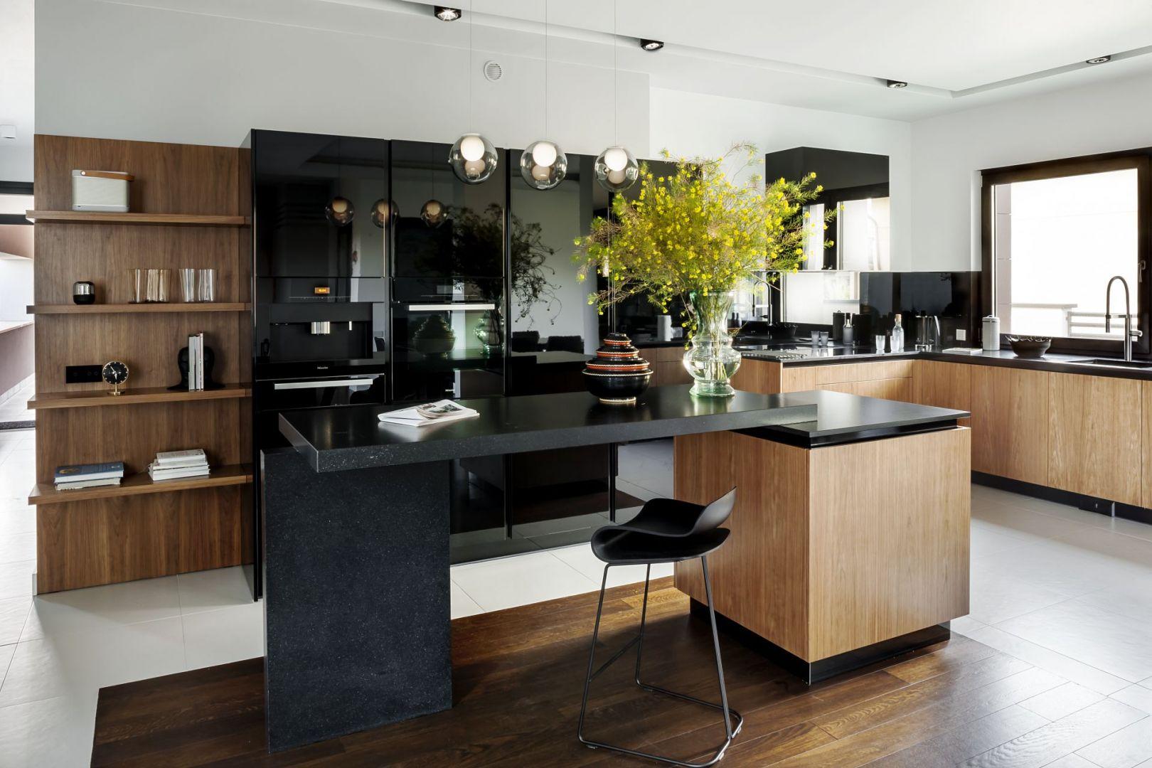Nie tylko biel dobrze komponuje się z drewnem. Czarne, lakierowane powierzchnie i drewno o karmelowym wybarwieniu sprawią, że wnętrze kuchni będzie niezwykle eleganckie. Fot. Zajc Kuchnie
