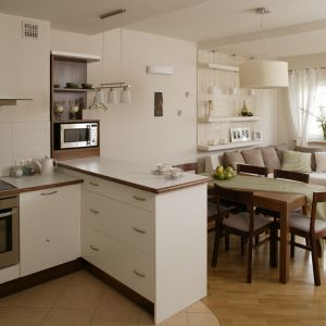 Kuchnia otwarta na salon utrzymana jest w jasnej tonacji. Białe matowe meble świetnie współgrają z białym ścianami oraz meblami w salonie. Wnętrze wydaje się bardzo przestronne. Projekt: Lucyna Stefaniak. Fot. Bartosz Jarosz