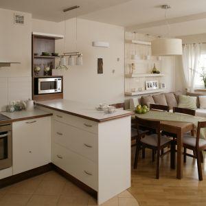 Kuchnia otwarta na salon utrzymana w jasnej, ale ciepłej tonacji. Białe matowe meble świetnie współgrają z białym ścianami oraz meblami. Wnętrze wydaje się bardzo przestronne. Projekt: Lucyna Stefaniak. Fot. Bartosz Jarosz