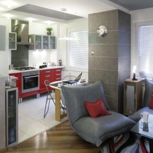 Elegancka kuchnia w bloku. Czerwone fronty dolnej zabudowy to ciekawy element wnętrza. Projekt: Liliana Masewicz-Kowalska. Fot. Monika Filipiuk-Obałek