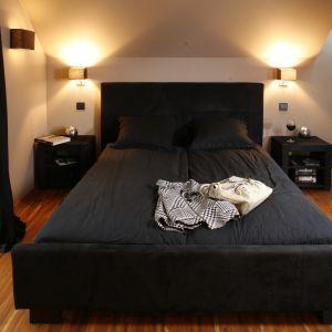 Czarne, tapicerowane łóżko z miękkim zagłówkiem to niebanalny element tego wnętrza. Sprawia, że sypialnia zachęca do wypoczynku. Projekt: Monika i Adam Bronikowscy. Fot. Bartosz Jarosz