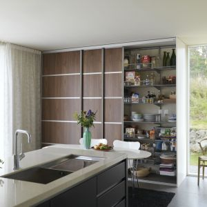 Drzwi przesuwne sprawiają, że wnętrze kuchni jest uporządkowane i minimalistyczne. Taka kuchenna szafa jest doskonałą alternatywą dla klasycznych szafek, jeśli chcesz urządzić kuchnię nowocześnie. Fot. Elfa
