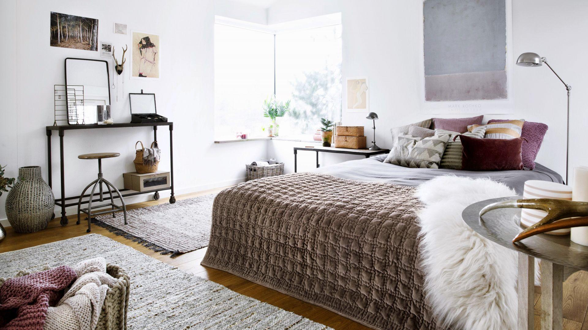 Jeśli chcesz, aby sypialnia była przytulna, a przy tym niebanalna, postaw na mocne faktury. Narzuta z wypukłymi wzorami czy futrzaste poduszki sprawią, że wnętrze nabierze charakteru. Fot. Broste Copenhagen