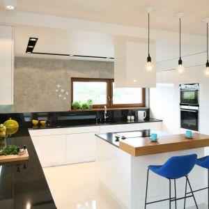 Czarno-biała aranżacja kuchni z elementami drewna. Wysokie stołki z kolorowymi siedziskami ożywiają wnętrze i nadają mu charakter. Projekt: Małgorzata Galewska. Fot. Bartosz Jarosz