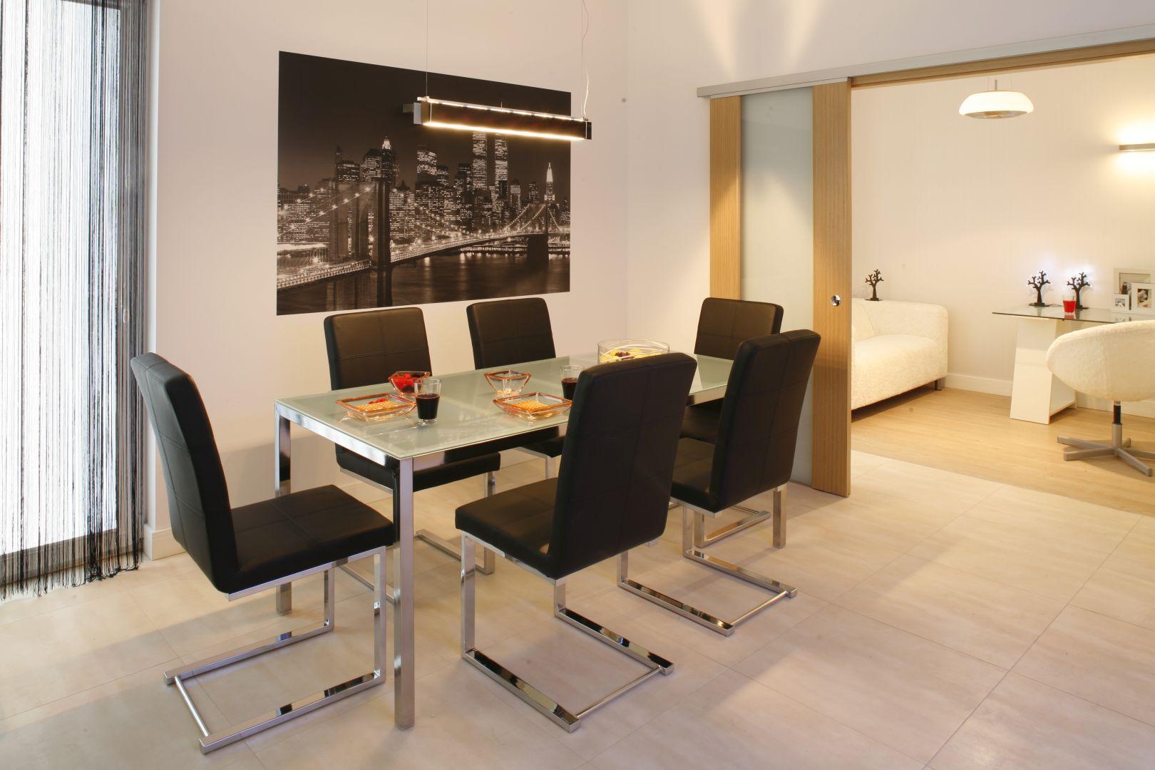 Prostokątny stół ze szklanym blatem na chromowanych nogach zestawiono z tapicerowanymi krzesłami z wysokim oparciem. Projekt: Patrycja Grych. Fot. Bartosz Jarosz
