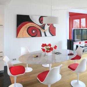Okrągły stół ze szklanym blatem i designerskie białe krzesła z czerwonym siedziskiem tworzą cały nastrój wnętrza. Projekt: Michał Mikołajczak. Fot. Bartosz Jarosz