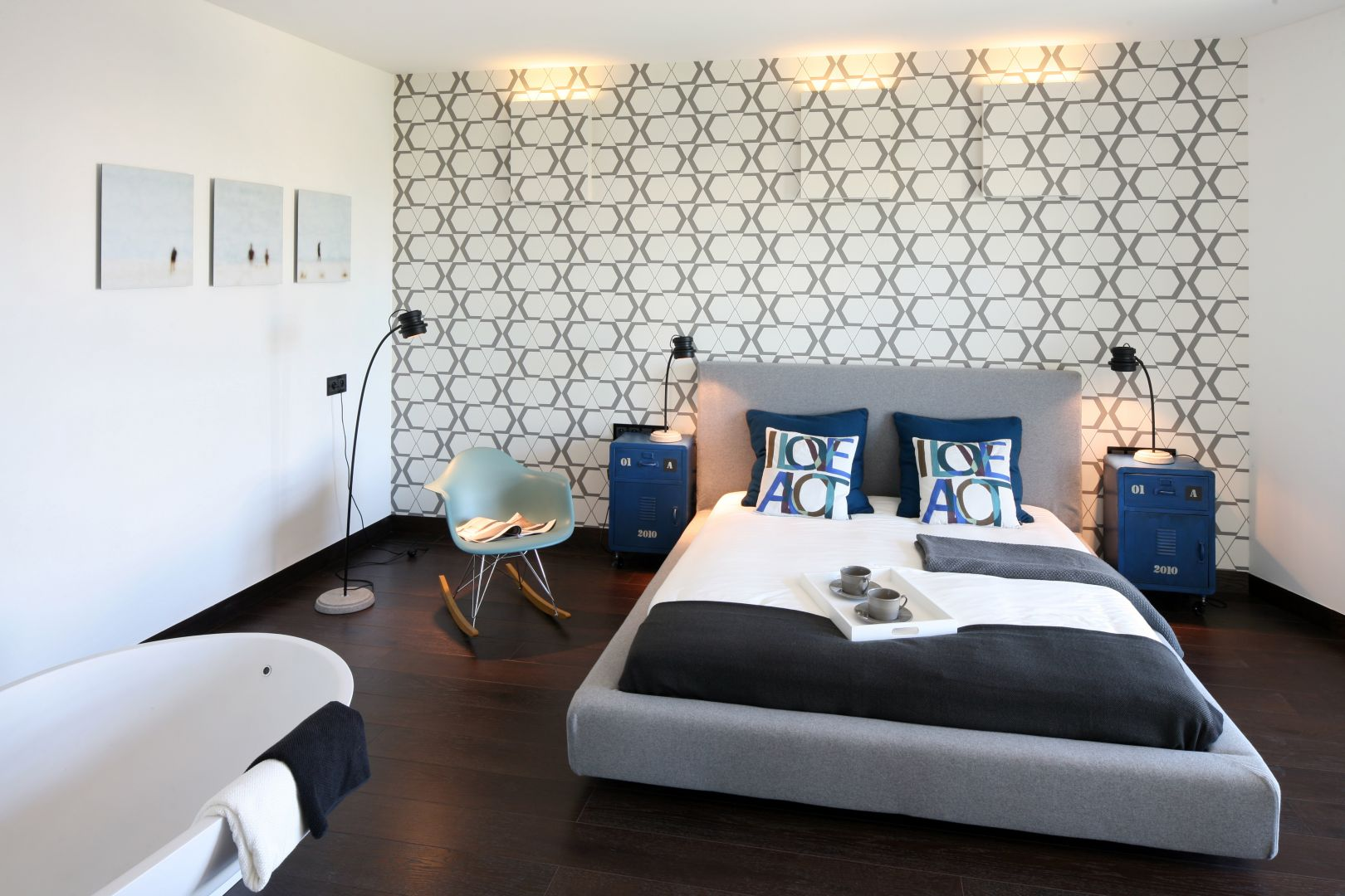 Szare tapicerowane łóżka to najnowszych krzyk mody. Mebel w zestawieniu z dekoracyjną tapetą oraz niebieskimi szafkami nocnymi prezentuje się bardzo gustownie. Projekt: Justyna Smolec. Fot. Bartosz Jarosz