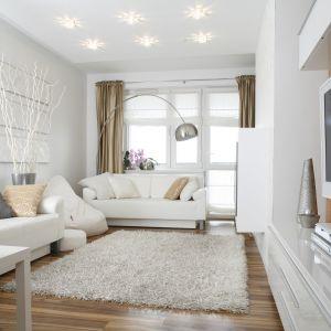 Jasny salon, urządzony w bieli.  białe sofy prezentują się szczególnie pięknie - mają niebanalny charakter i pięknie ozdabiają salon. Projekt: Małgorzata Mazur. Fot. Bartosz Jarosz