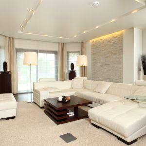 Podświetlona ściana wykończona cegłą oraz duża sofa to elementy, które nadają charakter temu wnętrzu. Rozłożysta sofa zapewnia komfort wypoczynku. Projekt: Anna Kuk-Dudka. Fot. Bartosz Jarosz