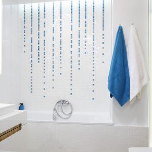Białą ścianę przy wannie ożywiono delikatnymi kafelkami w niebieskim kolorze. Ułożone są w taki sposób, że imitują spływające o ścianie krople wody. Projekt: Magdalena Kostrzewa-Świątek, Agnieszka Zaręba. Fot. Bartosz Jarosz