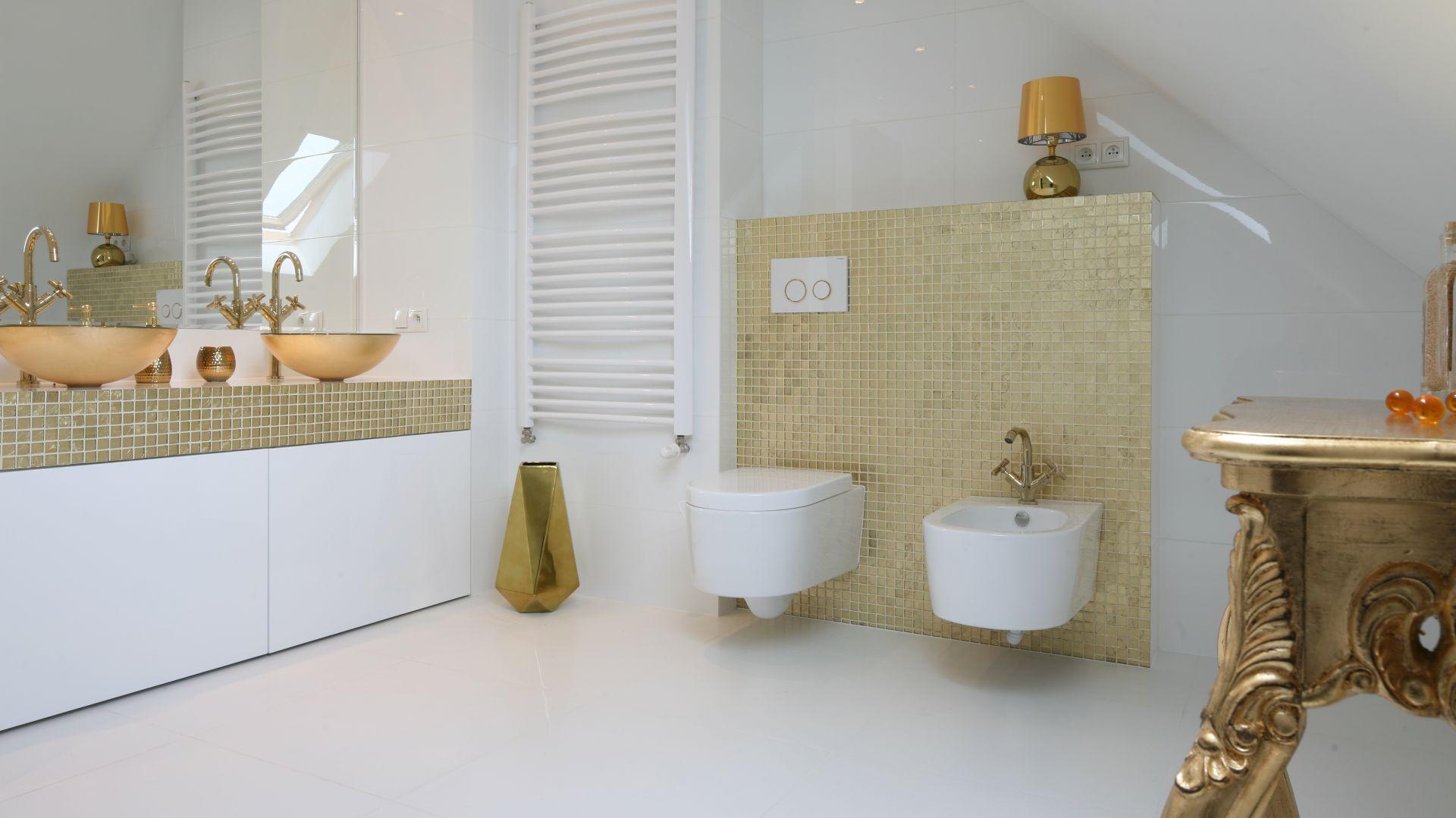 Biel jest fantastycznym tłem dla złotych dodatków. Dzięki nim łazienka będzie z pewnością jasna, stylowa i nowoczesna. Projekt: Piotr Stanisz. Fot. Bartosz Jarosz