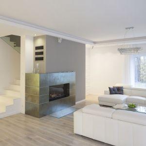 Salon urządzony w bieli można ożywić innym kolorem. Aby nie zdominował wnętrza, warto zastosować go jako dodatek, np. na jednej ze ścian. W tym domu ścianę kominkową wykończono subtelną szarością. Projekt: Katarzyna Mikulska-Sękalska. Fot. Bartosz Jarosz