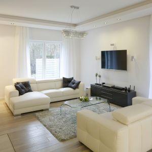 Salon w domu zaaranżowany w jasnej kolorystyce. Białe sofy, mimo że są dość dużych rozmiarów nie przytłaczają wizualnie wnętrza. Projekt: Katarzyna Mikulska-Sękalska. Fot. Bartosz Jarosz