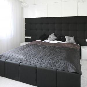 Sypialnia urządzona w czerni i bieli. Piękny dekoracyjny zagłówek rozciągnięty na całą szerokość ściany to ciekawy element wnętrza. Projekt: Dominik Respondek. Fot. Bartosz Jarosz