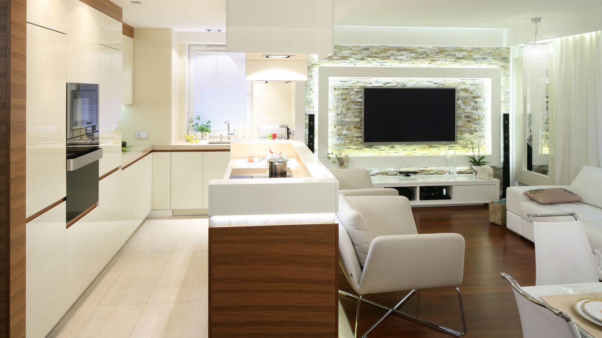 Salon i kuchnia mogą funkcjonować w doskonałej symbiozie. Wystarczy urządzić je w podobnej stylistyce, dzięki czemu pomieszczenie będzie spójne i harmonijne. Projekt; Małgorzata Mazur. Fot. Bartosz Jarosz.