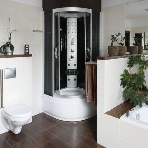 Biała łazienka z brązowymi elementami. W dużym pomieszczeniu zmieściła się wanna oraz kabina prysznicowa. Projekt: Joanna Wojtkielewicz. Fot. Bartosz Jarosz