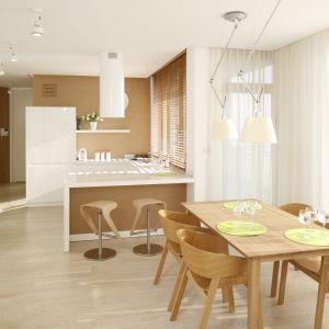 Przytulna kuchnia otwarta na salon. Drewniany stół harmonijnie komponuje się z barem wykończonym drewnem. Projekt: Maciej Brzostek. Fot. Bartosz Jarosz