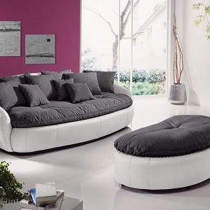 Aruba to sofa o nietypowym, zaokrąglonym kształcie. Sprawdzi się w nowoczesnym salonie. Do sofy można dokompletować okrągły puf. Fot. Cotta